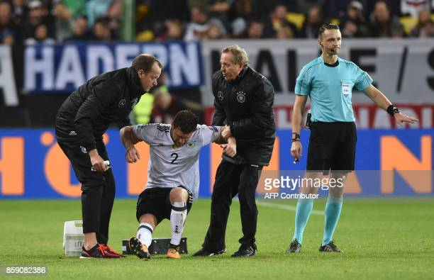 Medical staff help injured Germany's defender Shkodran Mustafi during the FIFA World Cup 2018 qualification football match between Germany and...