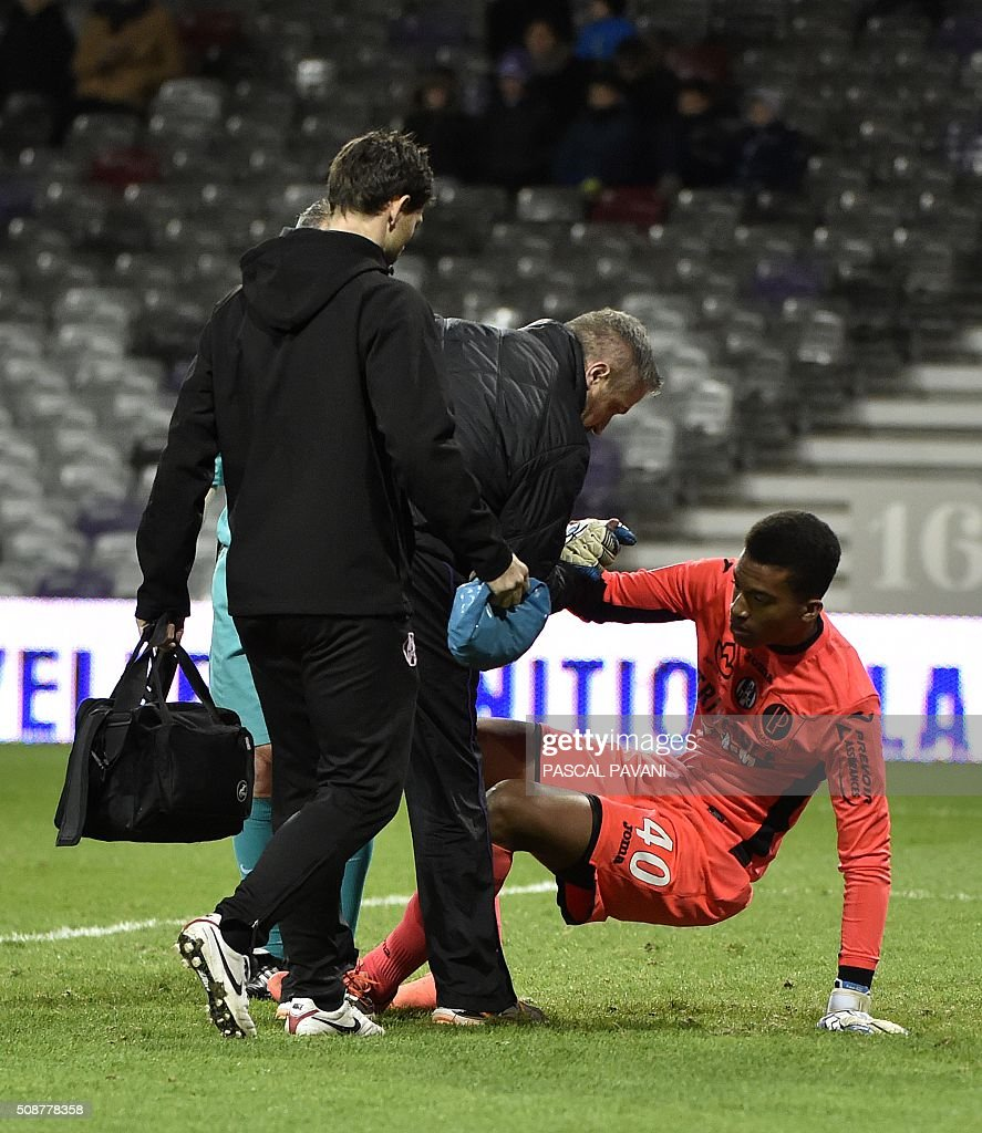 Medical staff help Toulouse's French goalkeeper Alban Lafont, after a knee injury during the French L1 football match Toulouse against Nantes on February 6, 2016 at the Municipal Stadium in Toulouse. AFP PHOTO / PASCAL PAVANI / AFP / PASCAL PAVANI