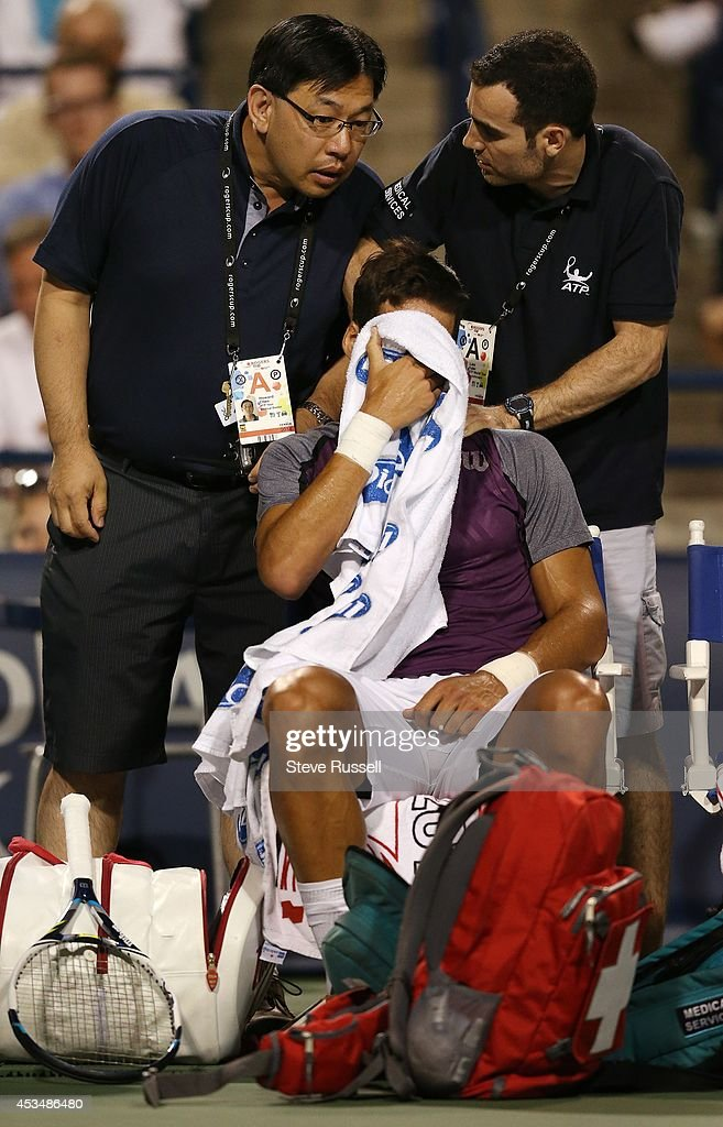 TORONTO, ON- AUGUST 9 - Medical staff look at Spaniard Feliciano Lopez's neck between games, he would fall to Roger Federer in straight sets in semi final action at the Rogers Cup Men's Tennis tournament at Rexall Centre at York University in Toronto. August 9, 2014. Steve Russell/Toronto Star
