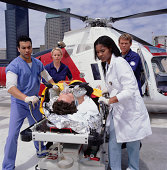 Medical staff moving patient on bed from rescue helicopter