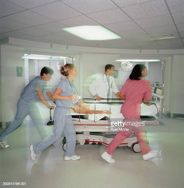 Medical staff moving patient on bed, in hospital corridor
