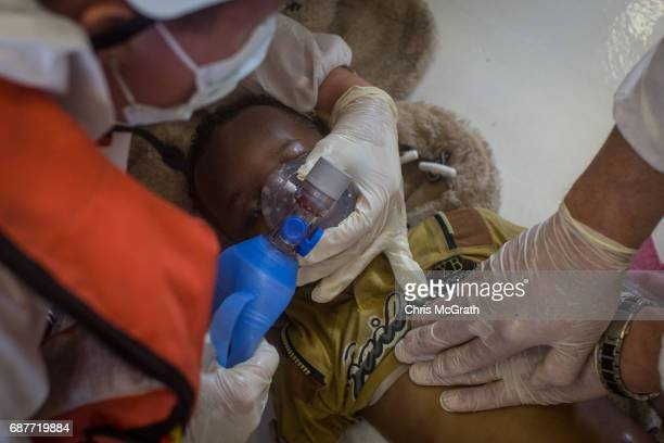 Medical staff of the Migrant Offshore Aid Station 'Phoenix' vessel perform CPR on a small child rescued from the sea after a wooden boat bound for...