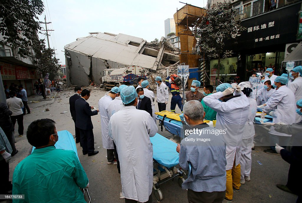 Medical staff prepare as rescuers search for buried people after a three-storey building collapsed on March 27, 2013 in Chengdu, China. The building in the process of demolition collapsed suddenly at around 6 p.m. on Wednesday, and the number of casualties remains unclear.