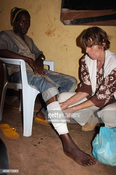 A medical staff treats displaced man's injured led outside Bangui Airport as Muslim families seek shelter under an aeroplane at Bangui Airport in...