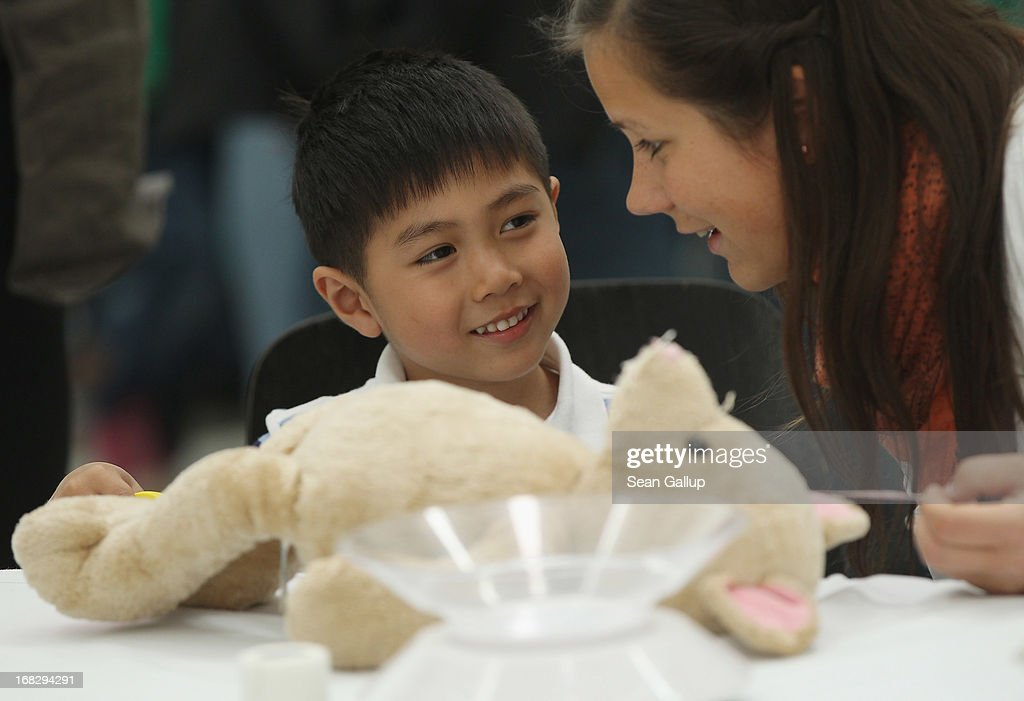 Medical student Alina Schwarz helps Phi Nam, 5, who was visiting with his mother, to diagnose his teddy bear at the Teddy Bear Clinic at Charite Hospital on May 8, 2013 in Berlin, Germany. Charite Hospital hosts the annual Teddy Bear Clinic days and invites children from Berlin day care centers to bring their injured teddy bears for fictitious examinations, x-rays, surgery and healing as a way for small children to become acquainted with a medical environment.