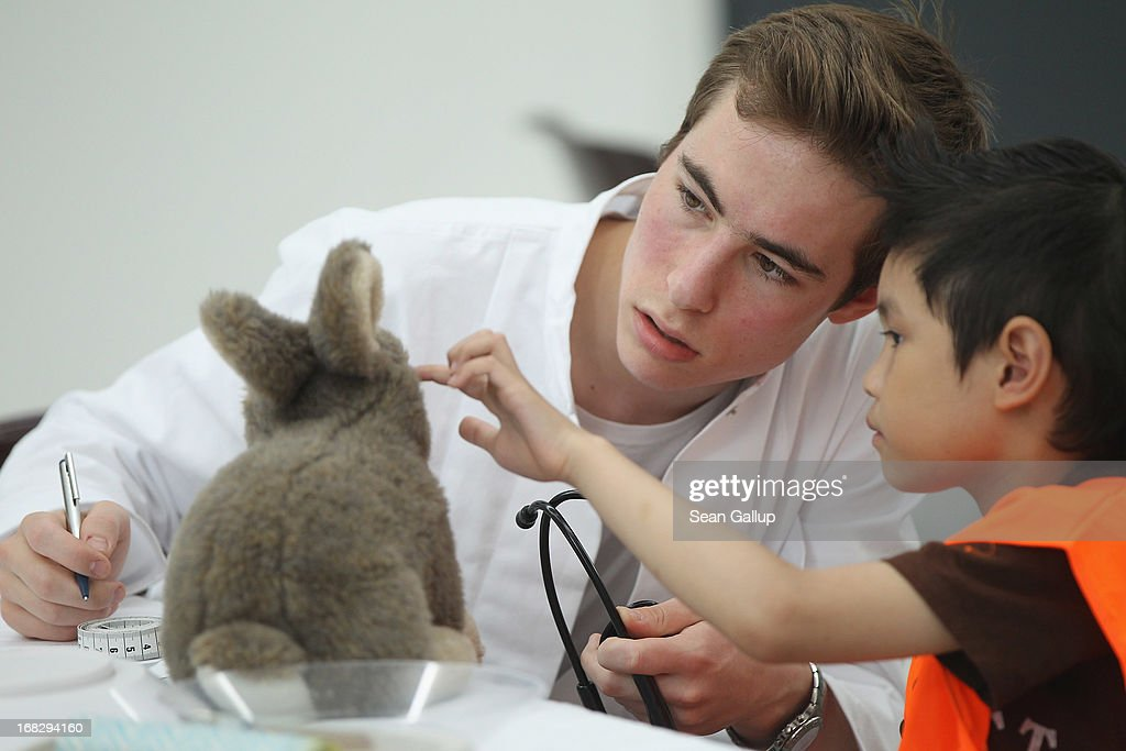 A medical student and a visiting little boy examine the boy's teddy rabbit at the Teddy Bear Clinic at Charite Hospital on May 8, 2013 in Berlin, Germany. Charite Hospital hosts the annual Teddy Bear Clinic days and invites children from Berlin day care centers to bring their injured teddy bears for fictitious examinations, x-rays, surgery and healing as a way for small children to become acquainted with a medical environment.