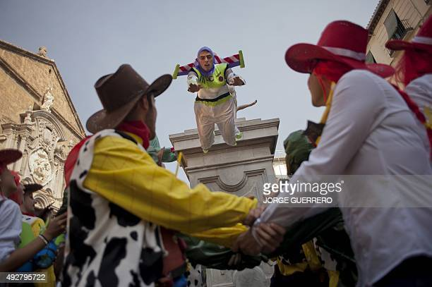 A medical student dressed up as US computer animation film studio Pixar's Toy Story character Buzz Lightyear is tossed by students during the faculty...