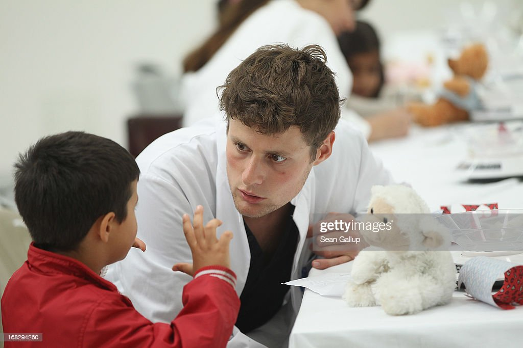 Medical student Jan Markus Diederich helps a visiting child to diagnose the child's teddy creature at the Teddy Bear Clinic at Charite Hospital on May 8, 2013 in Berlin, Germany. Charite Hospital hosts the annual Teddy Bear Clinic days and invites children from Berlin day care centers to bring their injured teddy bears for fictitious examinations, x-rays, surgery and healing as a way for small children to become acquainted with a medical environment.