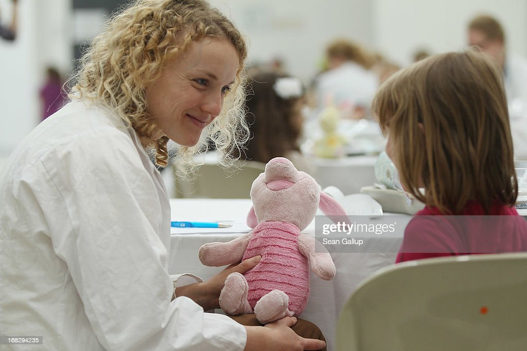 Medical student Marie Beer helps a visiting child to diagnose the child's teddy piglet at the Teddy Bear Clinic at Charite Hospital on May 8, 2013 in Berlin, Germany. Charite Hospital hosts the annual Teddy Bear Clinic days and invites children from Berlin day care centers to bring their injured teddy bears for fictitious examinations, x-rays, surgery and healing as a way for small children to become acquainted with a medical environment.