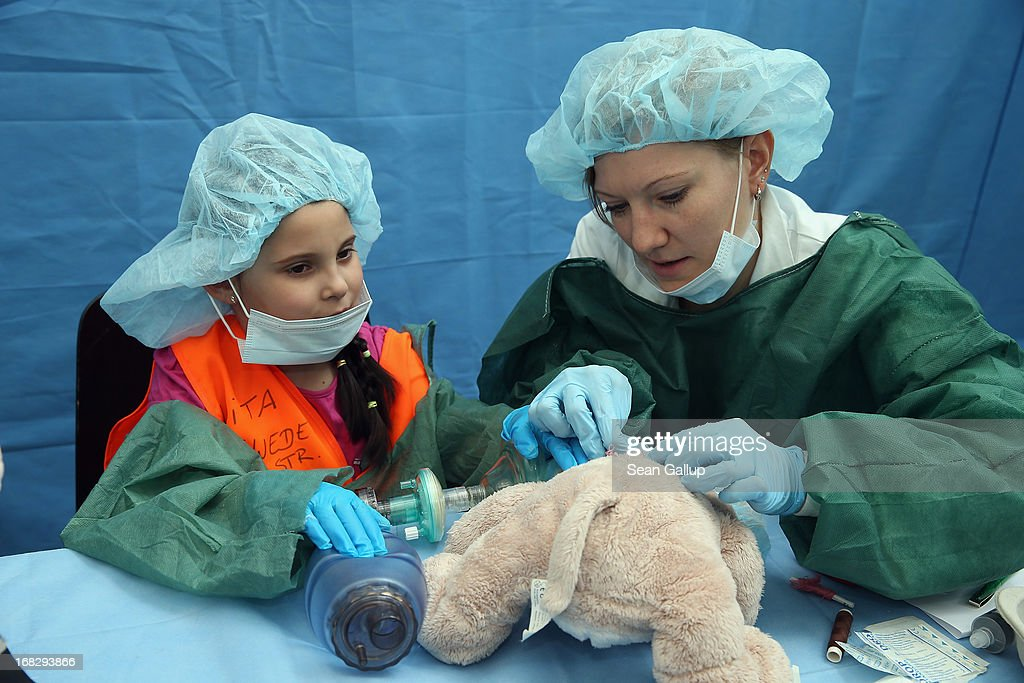 Medical student Natalie Schlueter helps Viktorija, 6, to sew up her teddy bear after fictitious surgery at the Teddy Bear Clinic at Charite Hospital on May 8, 2013 in Berlin, Germany. Charite Hospital hosts the annual Teddy Bear Clinic days and invites children from Berlin day care centers to bring their injured teddy bears for fictitious examinations, x-rays, surgery and healing as a way for small children to become acquainted with a medical environment.