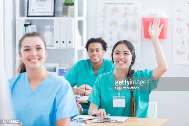 Medical student raises her hand in class to ask question