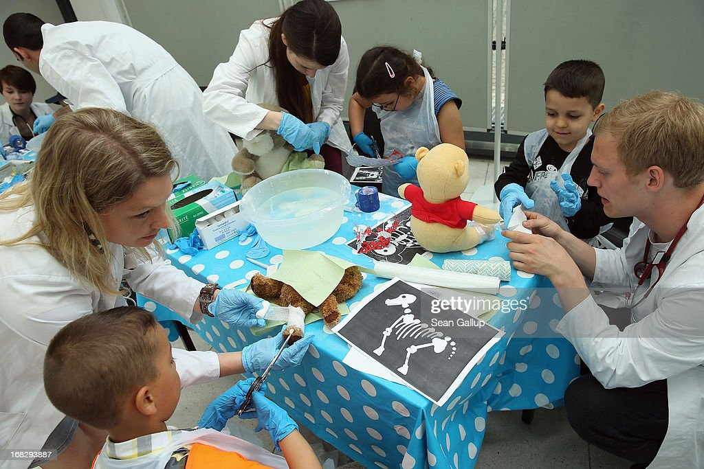 Medical students assist children in applying plaster casts to their stuffed animals at the Teddy Bear Clinic at Charite Hospital on May 8, 2013 in Berlin, Germany. Charite Hospital hosts the annual Teddy Bear Clinic days and invites children from Berlin day care centers to bring their injured teddy bears for fictitious examinations, x-rays, surgery and healing as a way for small children to become acquainted with a medical environment.