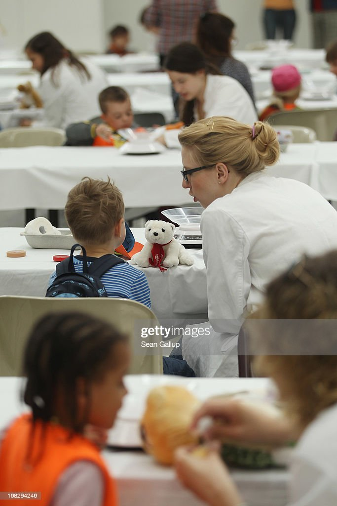 Medical students help visiting children diagnose their stuffed animals at the Teddy Bear Clinic at Charite Hospital on May 8, 2013 in Berlin, Germany. Charite Hospital hosts the annual Teddy Bear Clinic days and invites children from Berlin day care centers to bring their injured teddy bears for fictitious examinations, x-rays, surgery and healing as a way for small children to become acquainted with a medical environment.