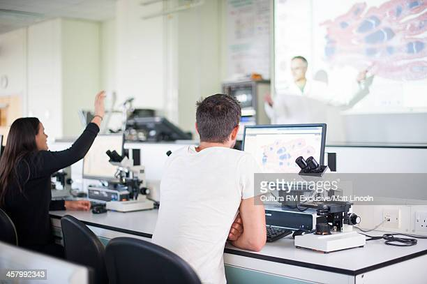 Medical students in lecture with overhead projector screen