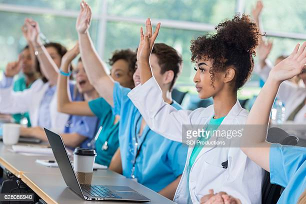Medical students raise hands in class