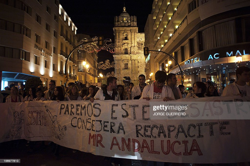 Medical students take part in a demonstration organized by health workers to denounce budget cuts and privatisations in health services, in Malaga of November 26, 2012. The health sector has been hard hit by the austerity policies implemented by the rightwing government of Mariano Rajoy, which is trying to cut the public deficit. The banner reads: 'Stop this disaster, Minister reconsider Andalucian MIR (resident physicians).'