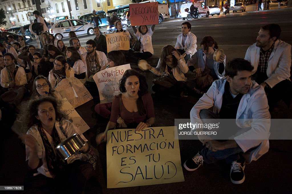 Medical students take part in a demonstration organized by health workers to denounce budget cuts and privatisations in health services, in Malaga of November 26, 2012. The health sector has been hard hit by the austerity policies implemented by the rightwing government of Mariano Rajoy, which is trying to cut the public deficit. The banner reads: 'Our traning is your health'