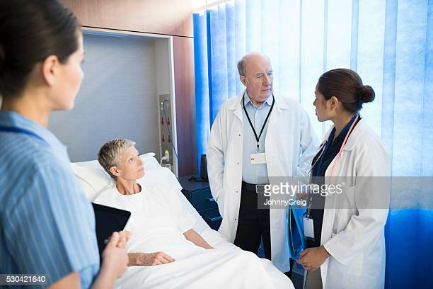 Medical team consulting with female patient in bed