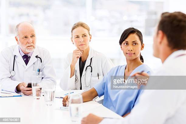 Medical Team Discussing At Table In Hospital