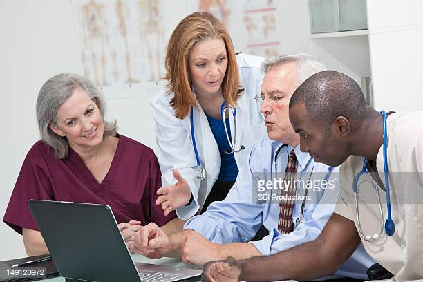 Medical Team Discussing Laptop Records in Doctors Office