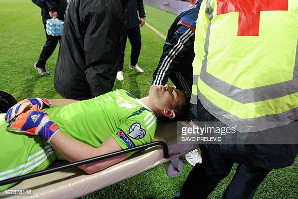 A medical team escorts Russia's goalkeeper Igor Akinfeev from the pitch after he was struck by a flare during the Euro 2016 group G qualifying...