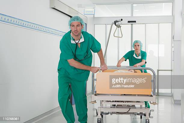 Medical team in scrubs with bed in hall