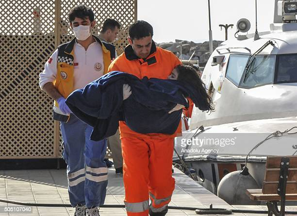 Medical team members carry a Afghan refugee child after a boat carrying refugees sank off on its way to Lesbos Island at Ayvacik district Canakkale...