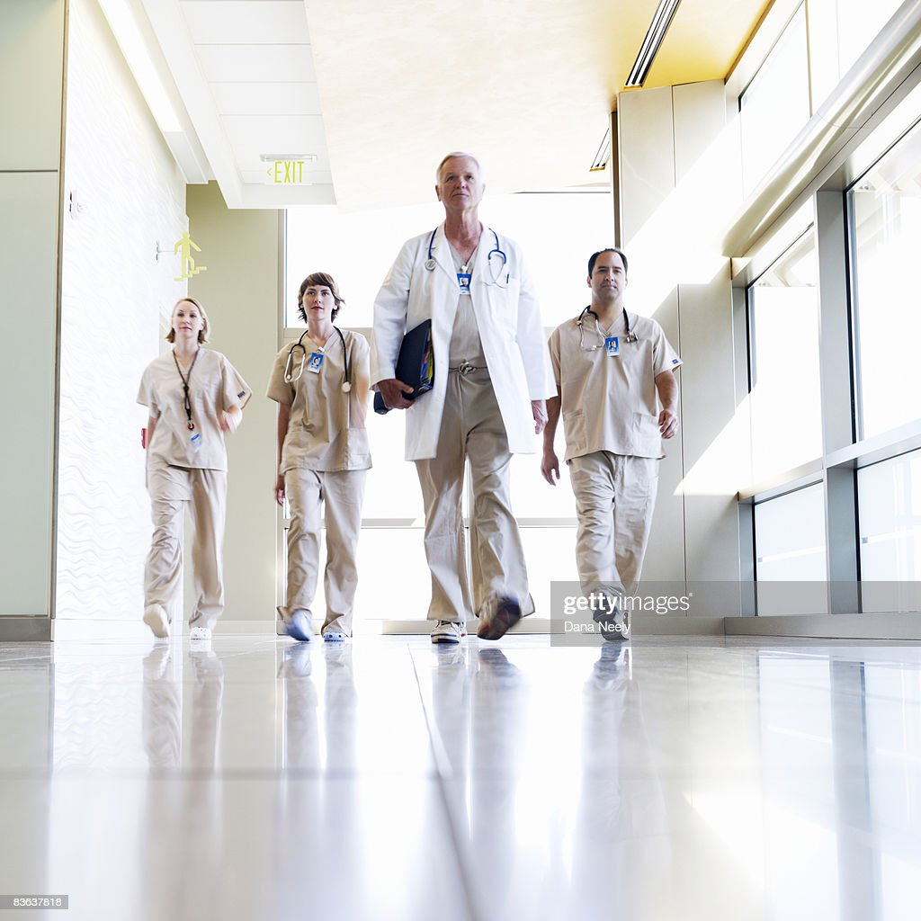 Medical team walking in hospital corridor  : Stock Photo