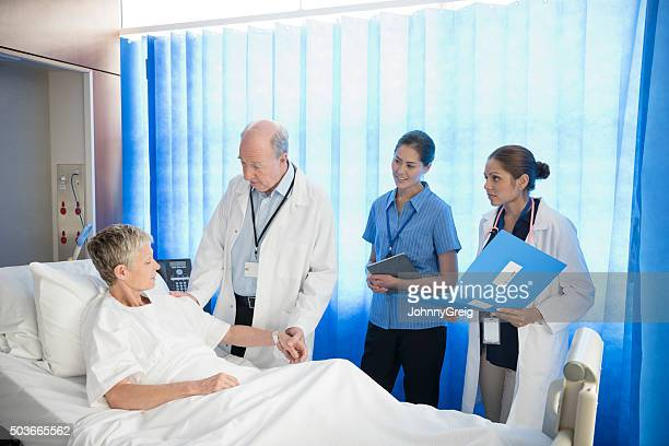 Medical team with mature patient in hospital bed