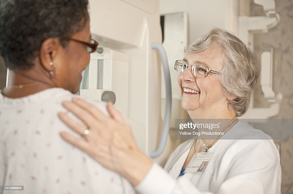 Medical Technician preparing Woman for Mammogram : Stock Photo