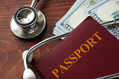Stethoscope with passport and dollar bills. Medical tourism concept.