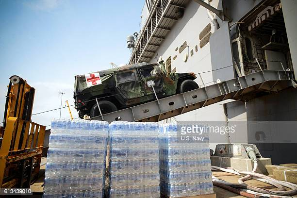 A medical vehicle attached to the 24th Marine Expeditionary Unit drives aboard the amphibious assault ship USS Iwo Jima during an onload of more than...