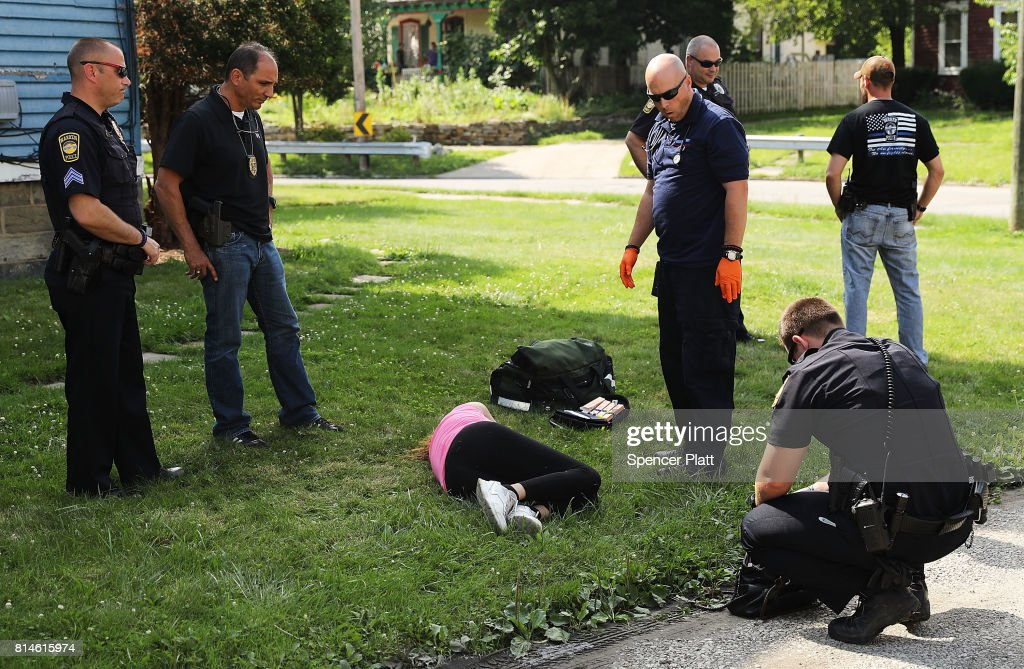 Medical workers and police treat a woman who has overdosed on heroin, the second case in a matter of minutes, on July 14, 2017 in Warren, Ohio. According to recent statistics, at least 4,149 Ohioans died from drug overdoses in 2016, a 36 percent leap from just the previous year and making Ohio the leader in the nation's overdose deaths.