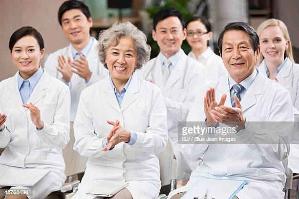 Medical workers clapping in a meeting