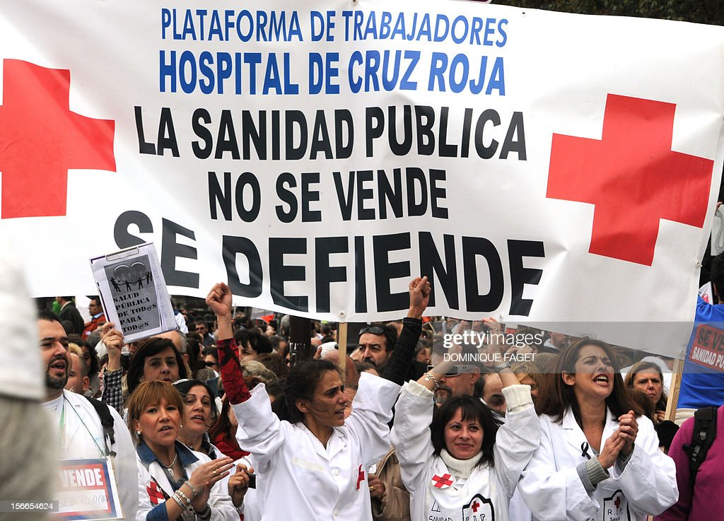 Medical workers hold a placard reading 'Health public services are not on sale' during a demonstration against the Spanish government's latest austerity measures in the center of Madrid on November 18, 2012. Thousands of medical workers gathered in Madrid to express their anger against the austerity measures. AFP PHOTO / DOMINIQUE FAGET