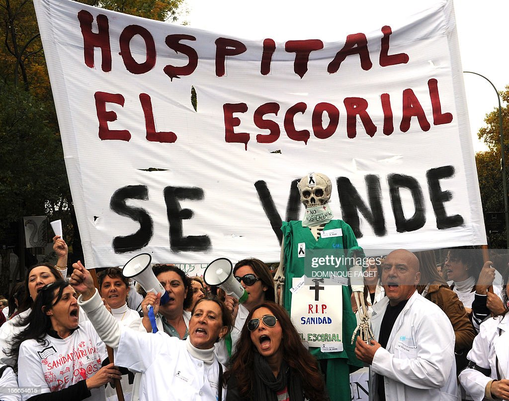 Medical workers hold a placard reading 'Hospital on sale' during a demonstration against the Spanish government's latest austerity measures in the center of Madrid on November 18, 2012. Thousands of medical workers gathered in Madrid to express their anger against the austerity measures.