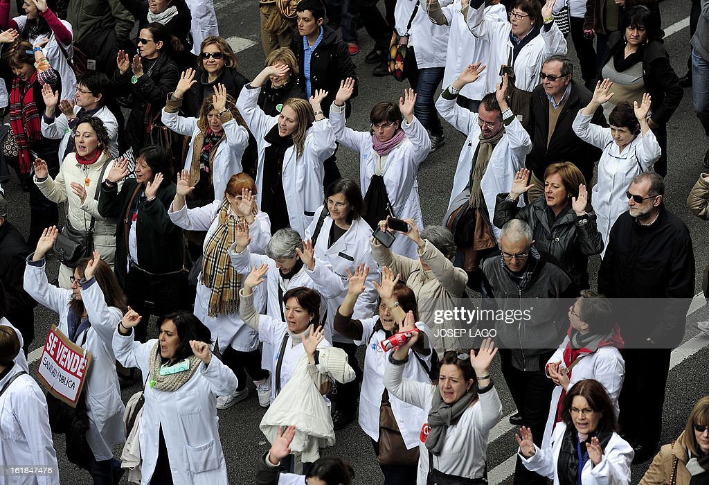 Medical workers take part in a demonstration against plans to cut medical spending and privatise hospital services in Barcelona on February 17, 2013. Thousands of Spanish doctors, nurses and other health care workers, many wearing white lab coats, demonstrated today in 16 cities against budget cuts and plans to partly privatise medical services. Nationally, Prime Minister Mariano Rajoy's government has slashed health spending by seven billion euros (9.1 billion USD) a year as part of a campaign to squeeze 102 billion euros out of the crisis-racked country's budget by 2014.
