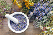 Medicinal herbs, mortar filled with healthy dry lavender flowers on wooden table. Herbal medicine. Top view, flat lay.