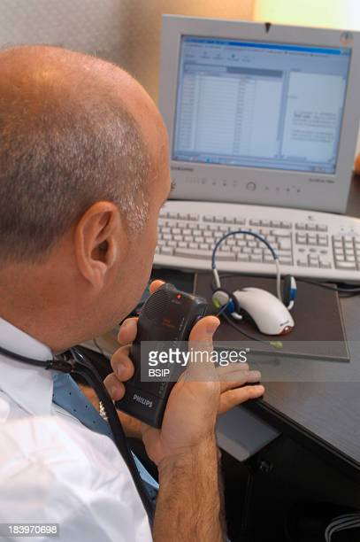 Medicine and Computer Science Cardiologists Office Consulting Patients History Recording Notes On Dictaphone