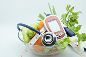 Medicine, diabetes, health care concept. Close up of Stethoscope with Glucose meter for check blood sugar level, lancet, tape measure and green vegetable fresh tomato, cucumber coriander and scallion.