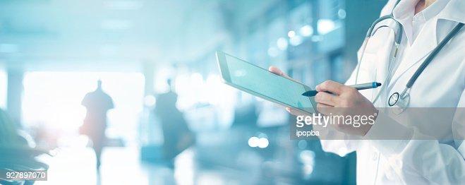 医学の医師と病院の背景にデジタル タブレットの医療情報ネットワーク接続インターフェイスに触れる聴診器。医療データと技術ネットワークの概念 : ストックフォト