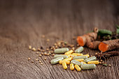 Medicine herb, Herbal capsule with healthy medicinal plant on wooden background