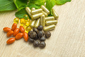 Herbal pills with healthy medical plant. Green leaf, alternative drug on wood ground