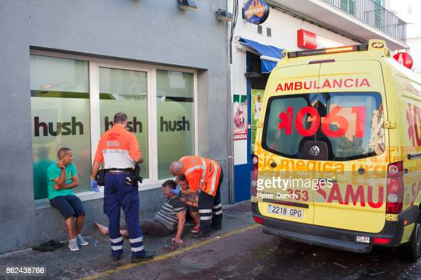 Medics attend to a man collapsed ooutside a bar in the West End area of San Antonio Ibiza