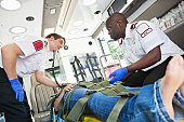 Medics caring for and working on patient in ambulance