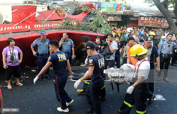 Medics carry a retrieve body from a bus that fell from an elevated highway in Manila on December 16 2013 Twentytwo people were killed when a commuter...