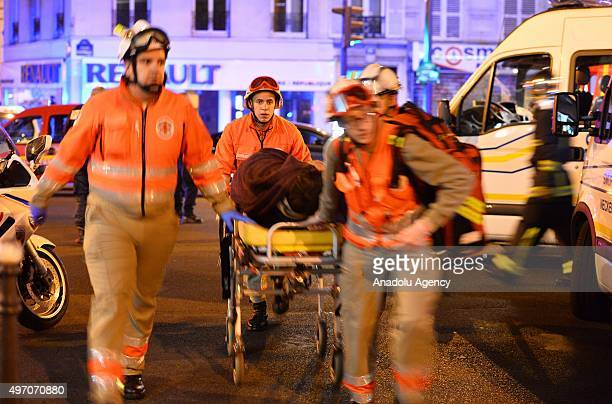 Medics carry the woundeds to the ambulances near Le Petit Cambodge restaurant in the 11th district after a driveby shooting killing 11 people...