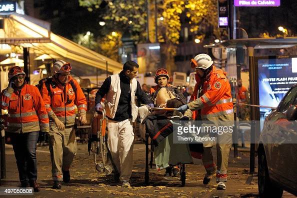 Medics evacuate an injured person on Boulevard des Filles du Calvaire close to the Bataclan theater early on November 14 2015 in Paris France...