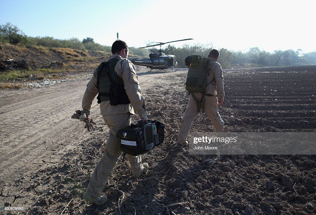 Medics from U.S. Air and Marine Operations (AMO), return to their helicopter after checking a sick immigrant caputured near the U.S.-Mexico border on December 10, 2015 at La Grulla, Texas. The number of families and unaccompanied minors illegally crossing the border from Central America has surged in recent months. Border security remains a key issue in the U.S. Presidential campaign.