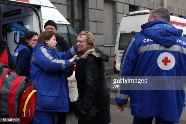 TOPSHOT Medics help an injured woman outside Technological Institute metro station in Saint Petersburg on April 3 2017 Around 10 people were feared...
